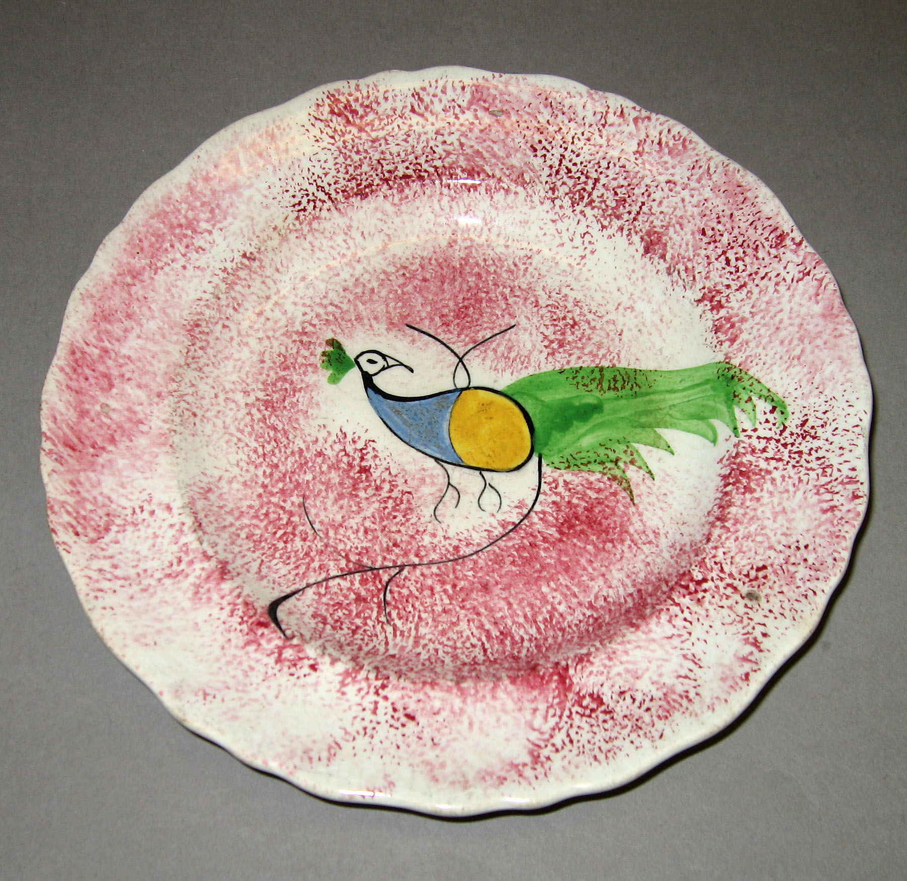 1965.0881.005 Pink spatter plate with peafowl pattern